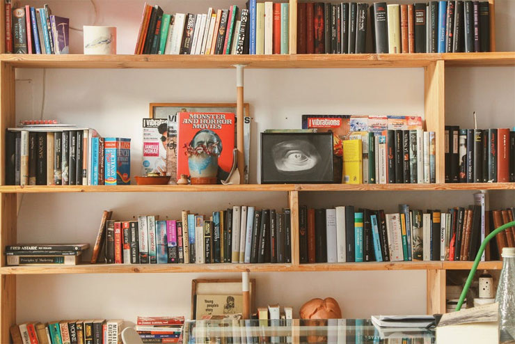 Books piled on a wooden bookshelf