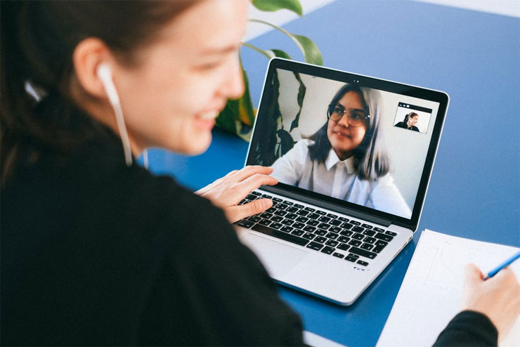 A woman smiling on a zoom call with another woman representing online engagement