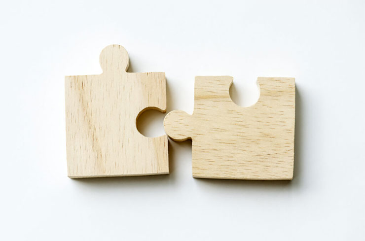 two wooden puzzle pieces half fitted together to represent common language for civic projects