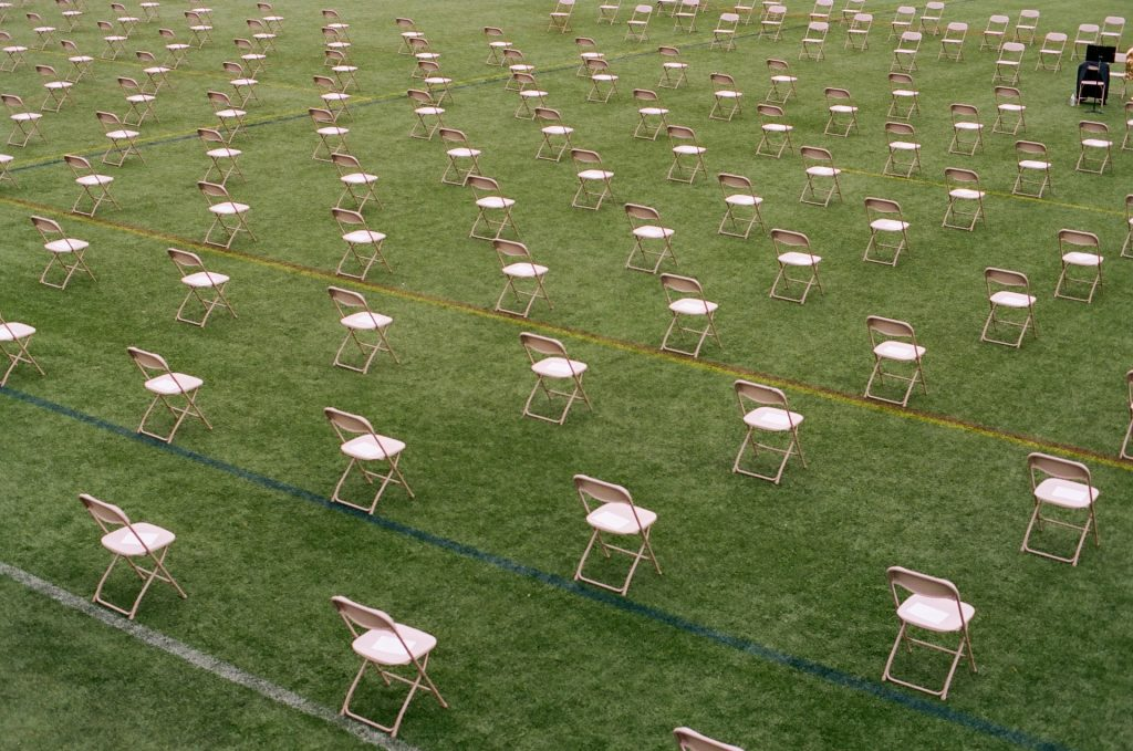 A forest of fold-out chairs on green astroturf to depict a world that is once again open for business